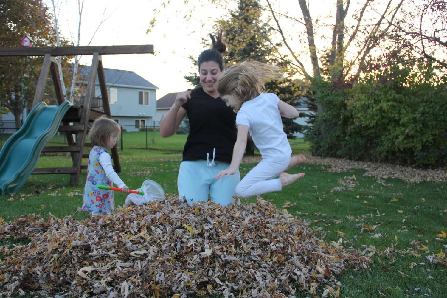 Au pair and host kids playing in the leaves